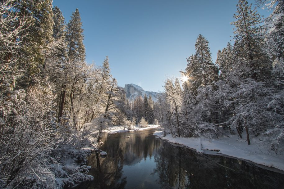 Yosemite valley covered in snow, Half dome in the distance a river in the foreground- Jeremy Bishop | Unsplash